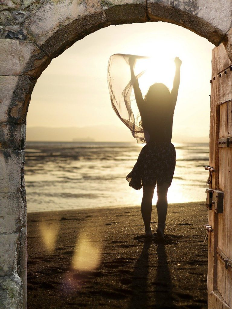 woman in doorway with arms in air, reaching to sun